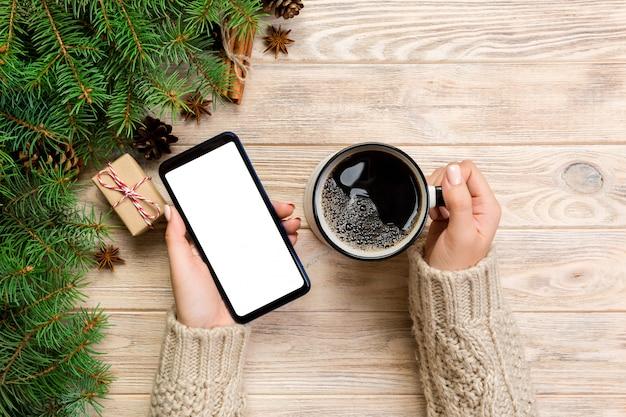Vrouwelijke handen die moderne smartphone en mok koffie op houten lijst houden