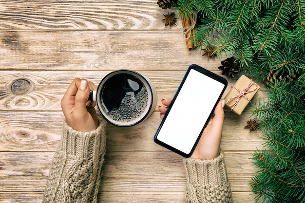 Vrouwelijke handen die moderne smartphone met mosk omhoog houden en mok koffie op houten uitstekende lijst met kerstmisdecoratie. bovenaanzicht