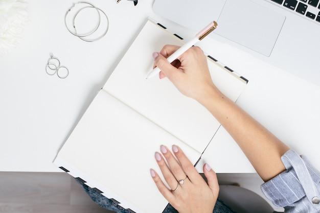 Vrouwelijke handen die nota's in een blocnote op een witte lijst met een laptop toetsenbord maken