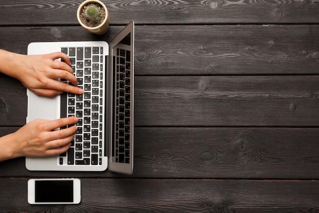 Vrouwelijke handen die op een laptop toetsenbord hoogste mening typen