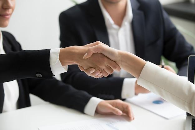 Vrouwelijke handen die op groepsvergadering schudden die vennootschapovereenkomst, close-up maken