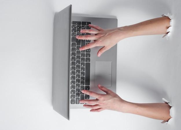 Vrouwelijke handen die op laptop toetsenbord typen
