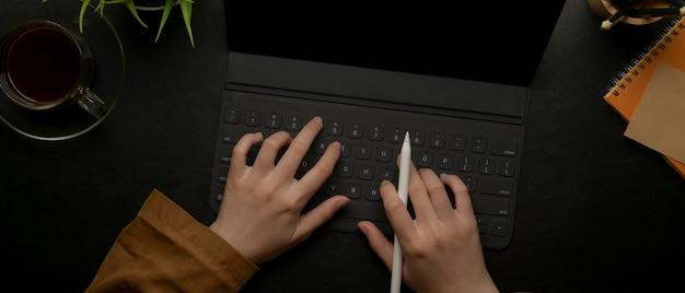 Vrouwelijke handen die op tablettoetsenbord typen op donker bureau met programmaboek en decoratie
