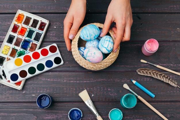 Vrouwelijke handen die paaseieren schilderen