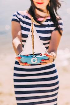 Vrouwelijke handen die papierboot op de zeeachtergrond houden