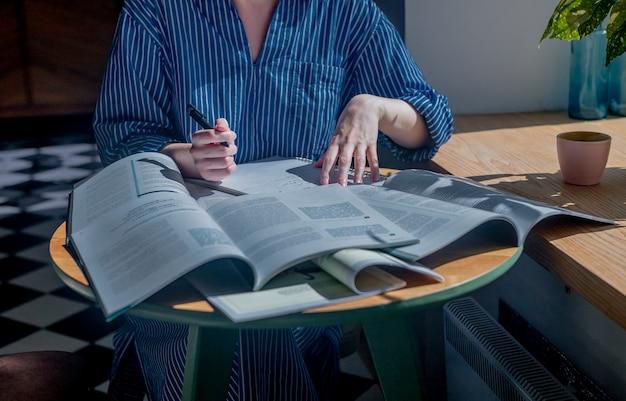 Vrouwelijke handen die pen vasthouden en veel boeken lezen concept van onderzoek en antwoorden zoeken in tekstb...