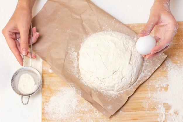 Vrouwelijke handen die pizzadeeg maken