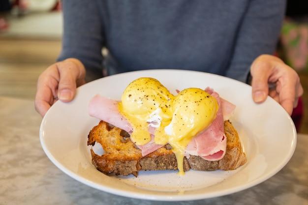 Vrouwelijke handen die plaat met ei benedict, ontbijtmaaltijd houden.