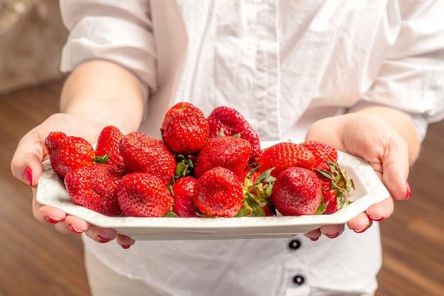 Vrouwelijke handen die plaat met smakelijke aardbeien houden