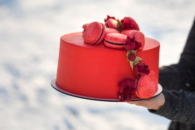 Vrouwelijke handen die plaat met verse heerlijke yummy eigengemaakte rode cake met macarons houden die met bloemen op vaag licht worden verfraaid