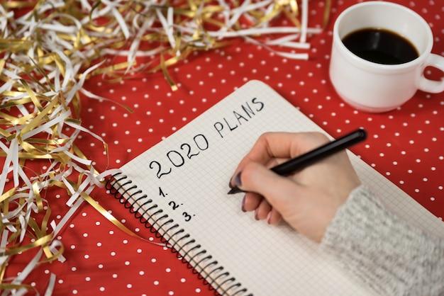 Vrouwelijke handen die plannen in een notitieboekje schrijven.