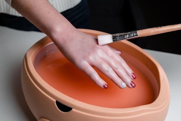 Vrouwelijke handen die procedure in een lilac paraffinekom nemen. cosmetische en huidverzorgingsapparatuur in een schoonheidssalon.