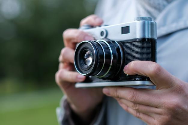 Vrouwelijke handen die retro fotocamera vóór zich houden en snapshots nemen.