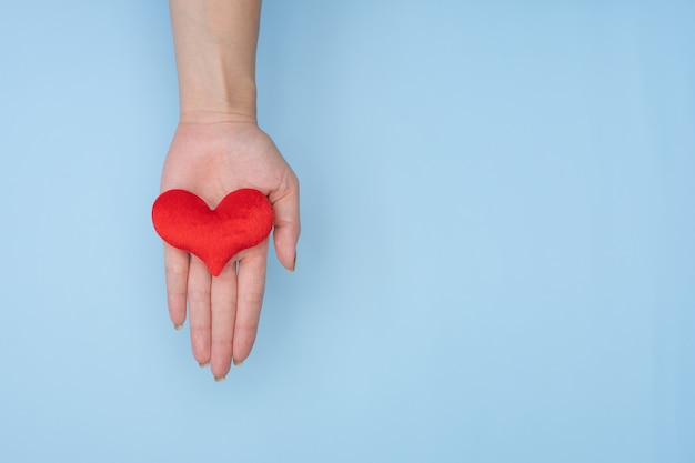 Vrouwelijke handen die rood hart op blauwe achtergrond geven.
