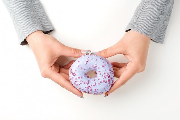 Vrouwelijke handen die smakelijke doughnut houden met bestrooit