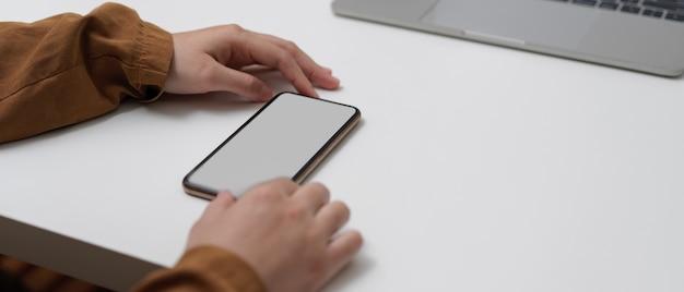 Vrouwelijke handen die spot op smartphone op werktafel met laptop in huisbureau gebruiken