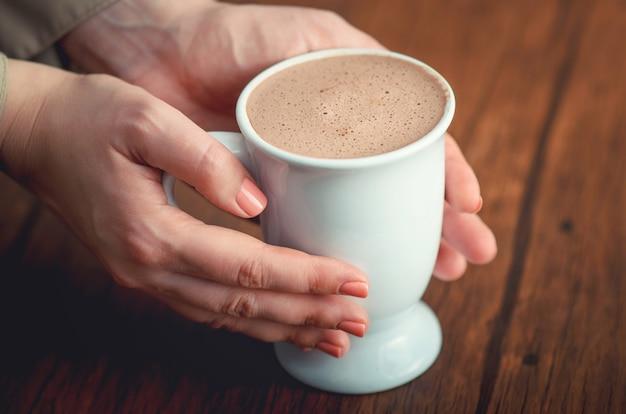 Vrouwelijke handen die teder kopje cacao op het houten bureau houden.