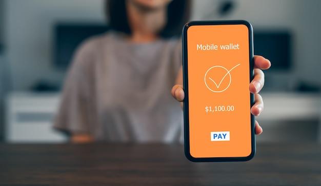 Vrouwelijke handen die telefoon met betalings mobiel bankwezen online gebruiken.