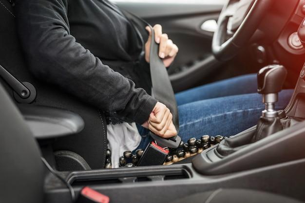 Vrouwelijke handen die veiligheidsgordel in auto vastmaken