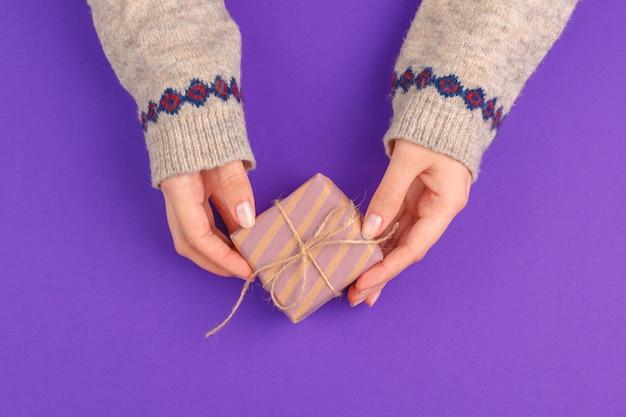 Vrouwelijke handen die verpakte gift op purpere achtergrond houden