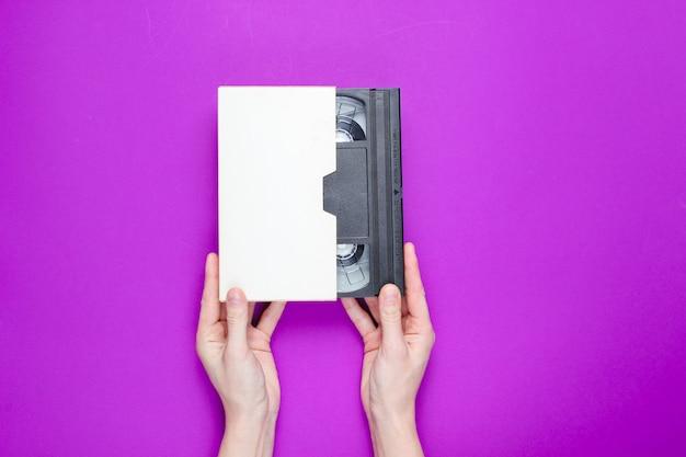 Vrouwelijke handen die videocassette in dekking op purpere achtergrond houden