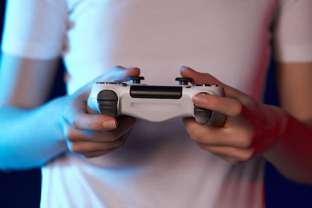 Vrouwelijke handen die videospelletjes spelen op de console, close-up. neonverlichting