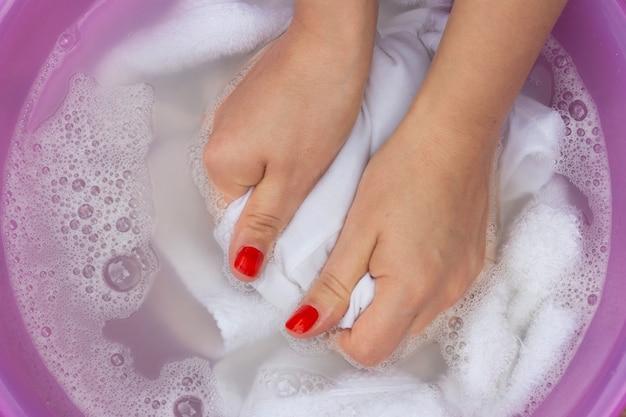 Vrouwelijke handen die witte kleren in bassin wassen