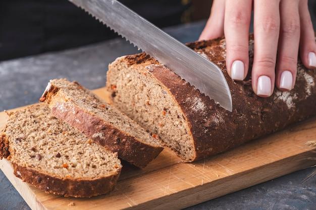 Vrouwelijke handen die wortelbrood op de houten raad snijden.