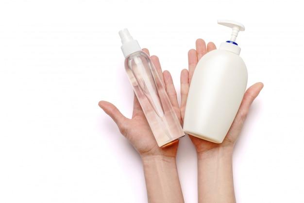Vrouwelijke handen die zeep en handdesinfecterende middelnevelautomaat houden die op witte achtergrond met het knippen van weg wordt geïsoleerd