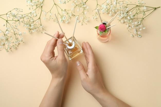 Vrouwelijke handen, diffusers en bloemen op beige achtergrond