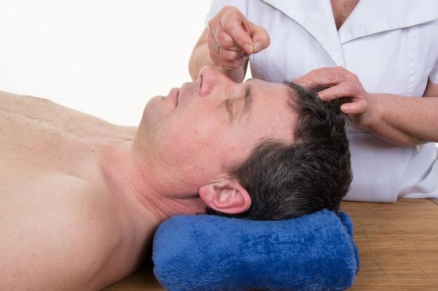 Vrouwelijke handen doen acupunctuur van oor