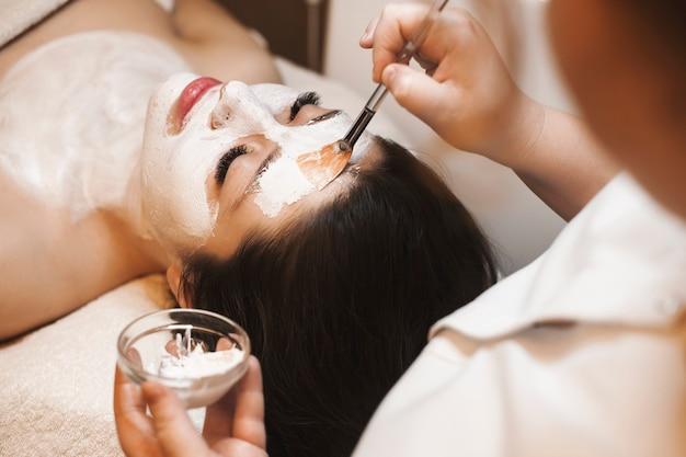 Vrouwelijke handen doen een wit huidverzorgingsmasker op een vrouwelijk gezicht in een wellness-salon.