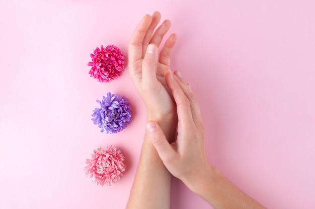 Vrouwelijke handen en bloemen. huid- en handverzorging. hydrateert en elimineert de droogheid van de handenhuid