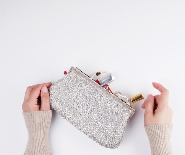 Vrouwelijke handen en een zilveren cosmetische tas met cosmetica