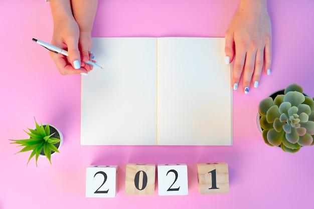 Vrouwelijke handen en handsof een kind met houten kubussen van het jaar 2021 boven roze achtergrond