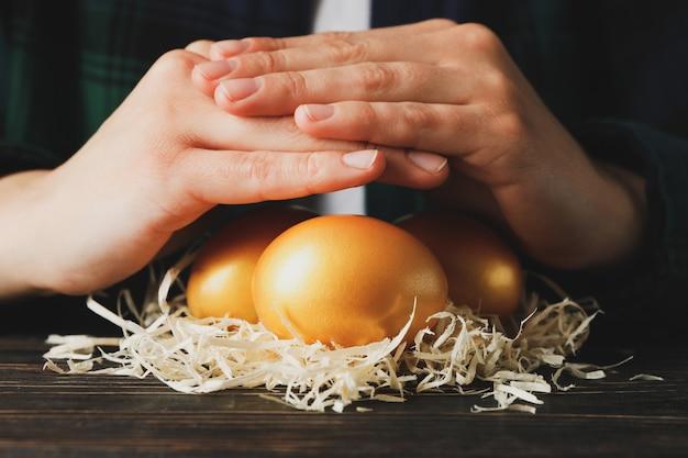 Vrouwelijke handen en nest met gouden eieren op houten tafel