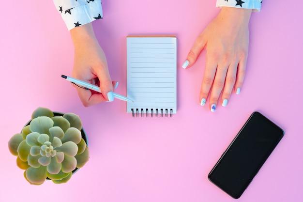 Vrouwelijke handen en open kladblok op roze bovenaanzicht