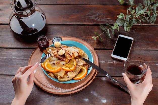 Vrouwelijke handen en pannenkoeken met sap. gezond ontbijt
