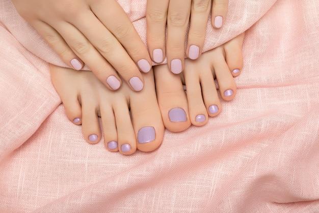 Vrouwelijke handen en voeten met roze nageldesign op roze stof.