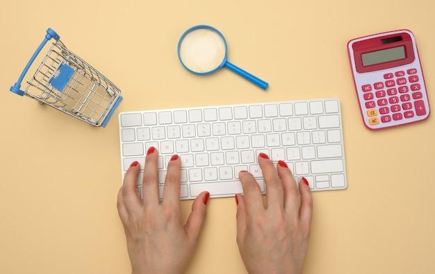 Vrouwelijke handen en wit draadloos toetsenbord, stapel papieren bonnen en vergrootglas op gele achtergrond, concept voor budgetanalyse, besparingen