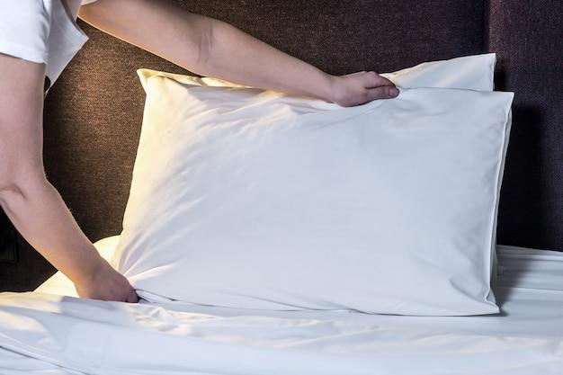Vrouwelijke handen gecorrigeerd kussen op het bed
