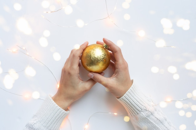 Vrouwelijke handen, gekleed in een witte trui, houden een gouden kerstbal vast in bokehlichten.