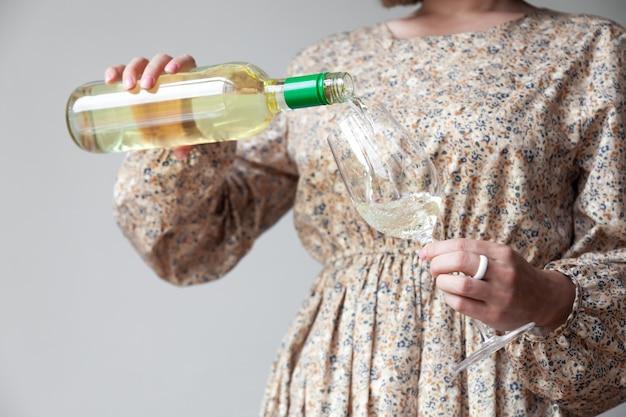 Vrouwelijke handen gieten witte wijn van fles tot glas