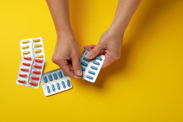 Vrouwelijke handen houden blisterverpakking met pillen geïsoleerd