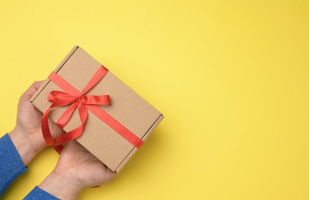 Vrouwelijke handen houden bruine kartonnen doos met rood lint, bovenaanzicht, kopie ruimte