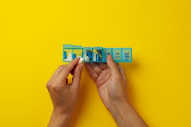 Vrouwelijke handen houden container met pillen op geel
