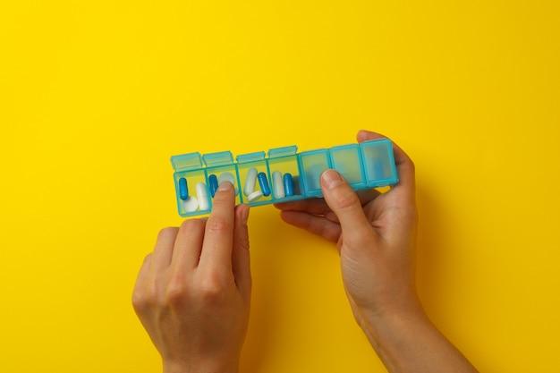 Vrouwelijke handen houden container met pillen