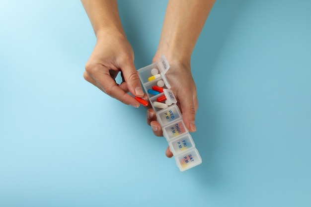 Vrouwelijke handen houden containers met pillen op blauw