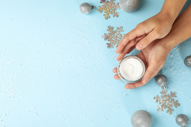 Vrouwelijke handen houden cosmetische crème geïsoleerd met kerstballen