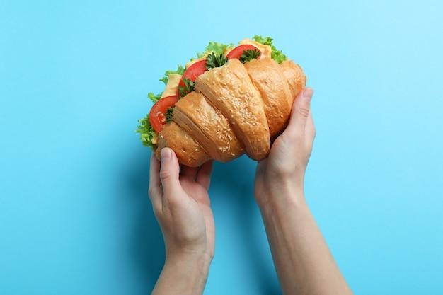 Vrouwelijke handen houden croissantsandwich op blauw